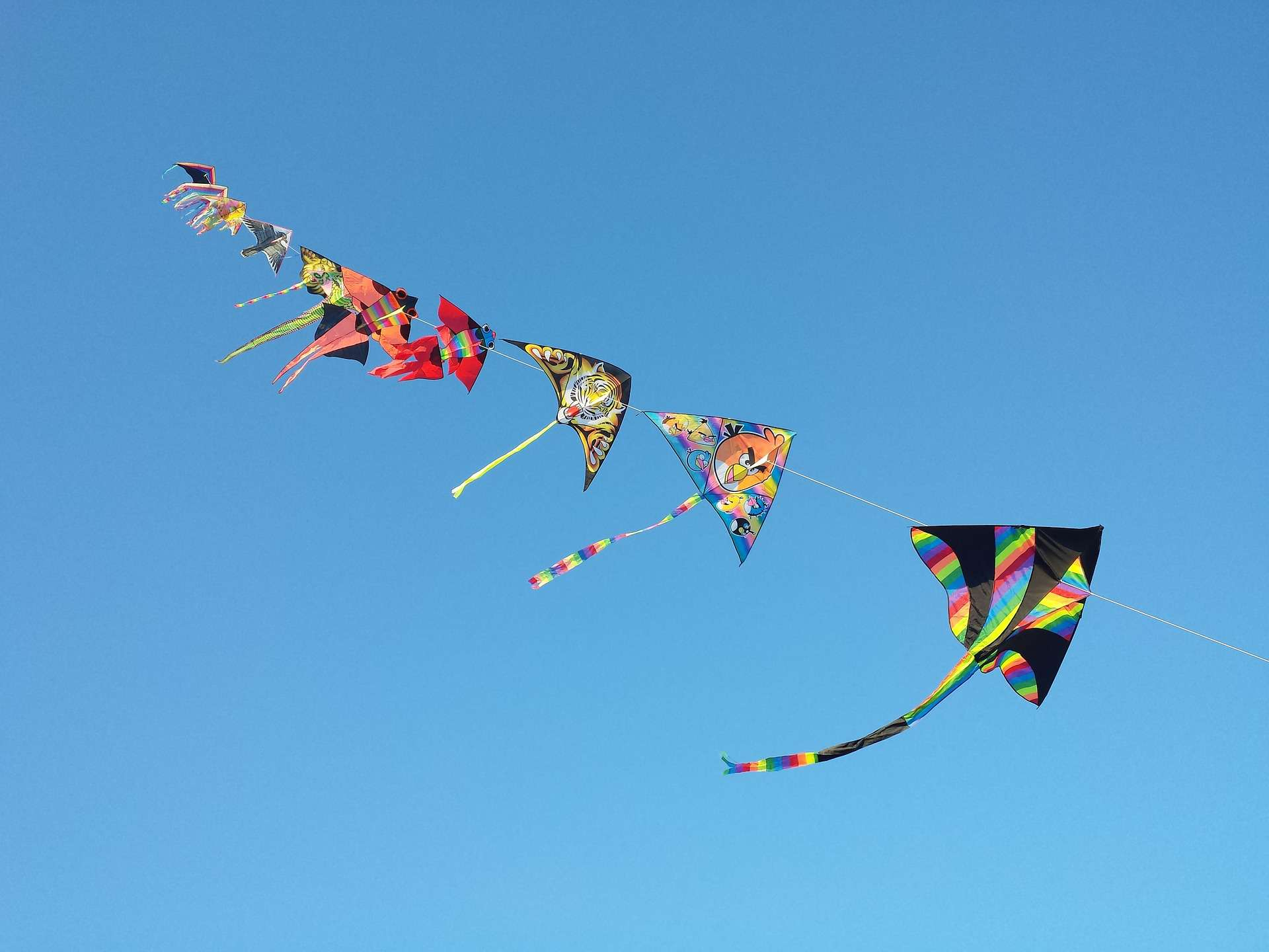 Colorful paper kites against a cloudless blue sky.