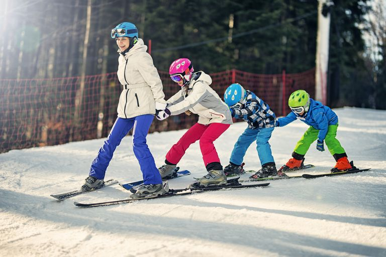 f92e1e9e9c Kids practicing skiing with ski school instructor