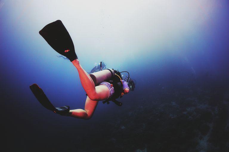 Scuba diver swimming into the blue