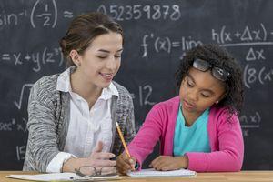 Math teacher helps elementary schoolgirl with math assignment
