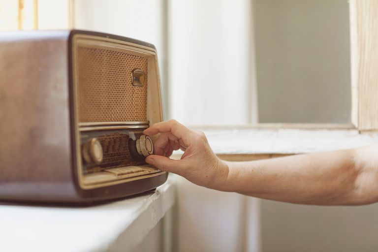 Woman uses an old traditional radio