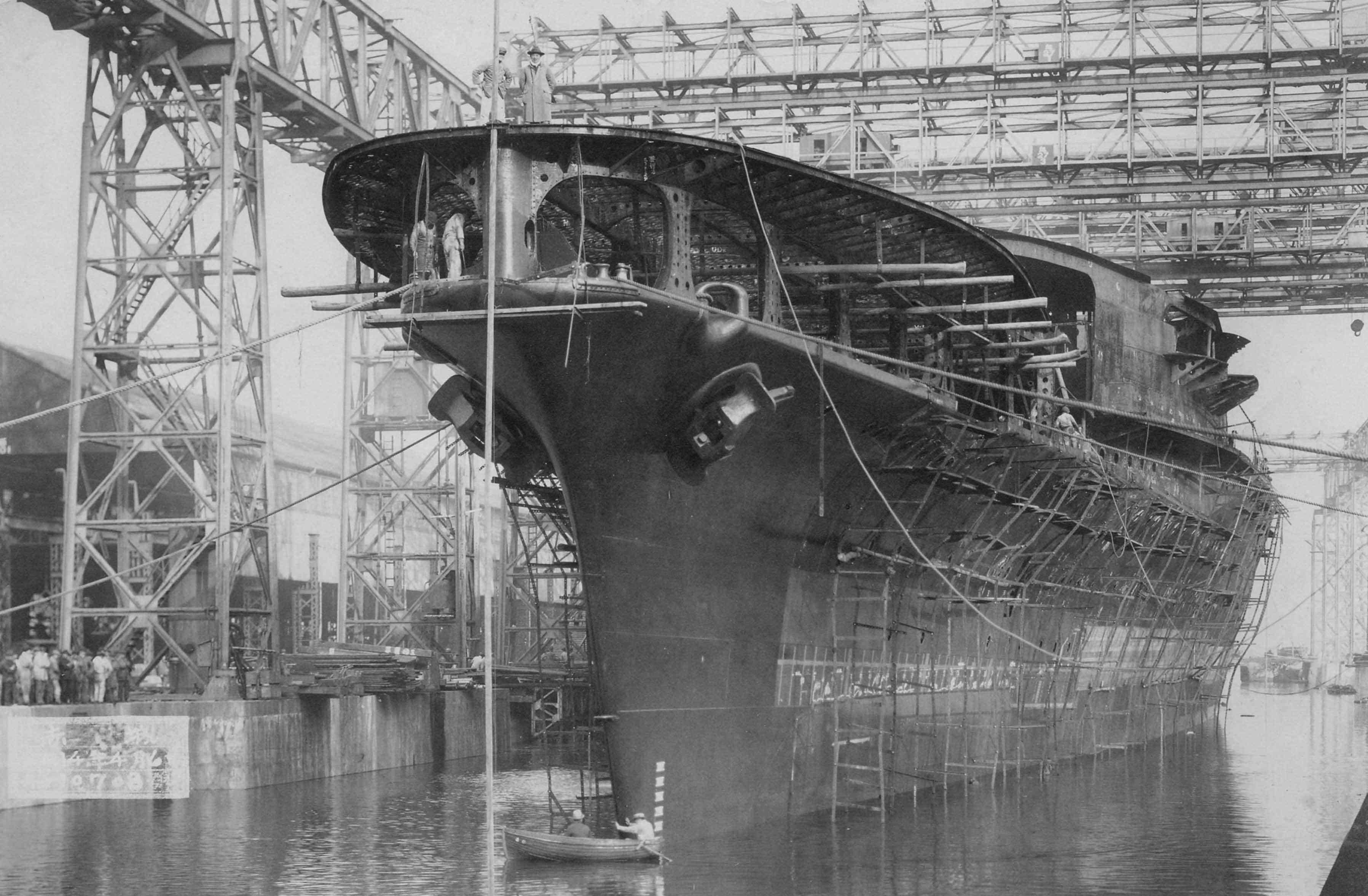 Unfinished hull of carrier Akagi after its launch near a dock.