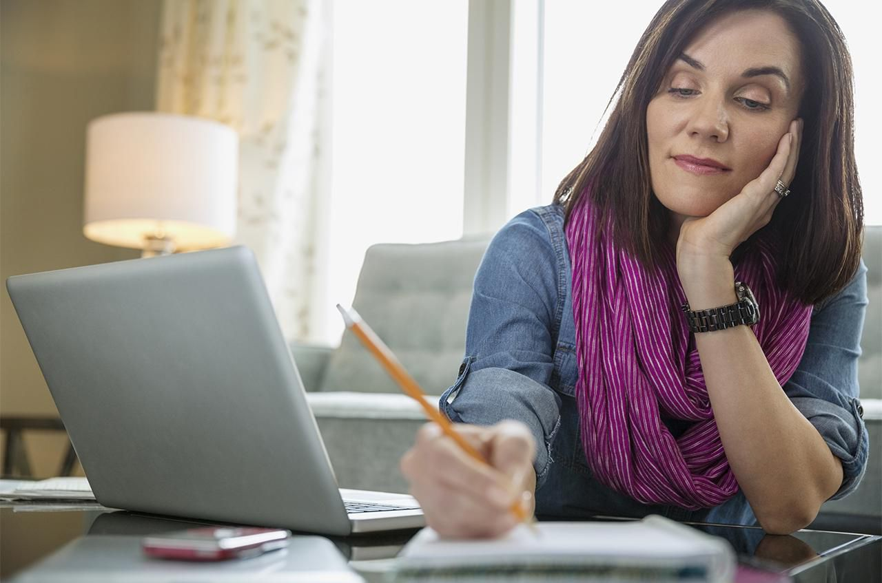 woman with laptop writing in book at table