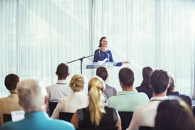 Businesswoman giving a speech at a podium to a crowd