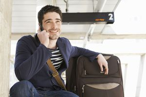 Guy with luggage talking on mobile phone