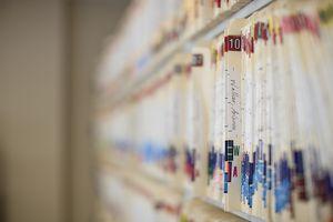 Patient records in folders on a shelf