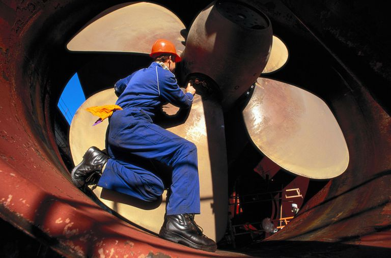 Worker by ship propeller in Norway.