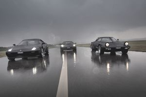 Group of GT cars driving at speed on a wet road