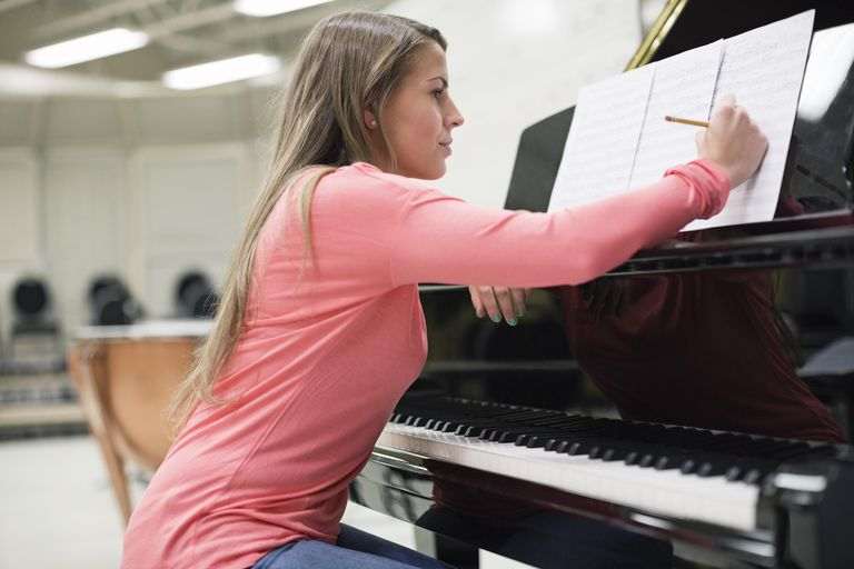 Female student writing on sheet music in college music room
