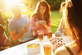 friends playing cards in the evening sun