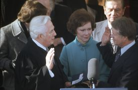 Jimmy Carter taking the oath of office with the Chief Justice and his wife standing by