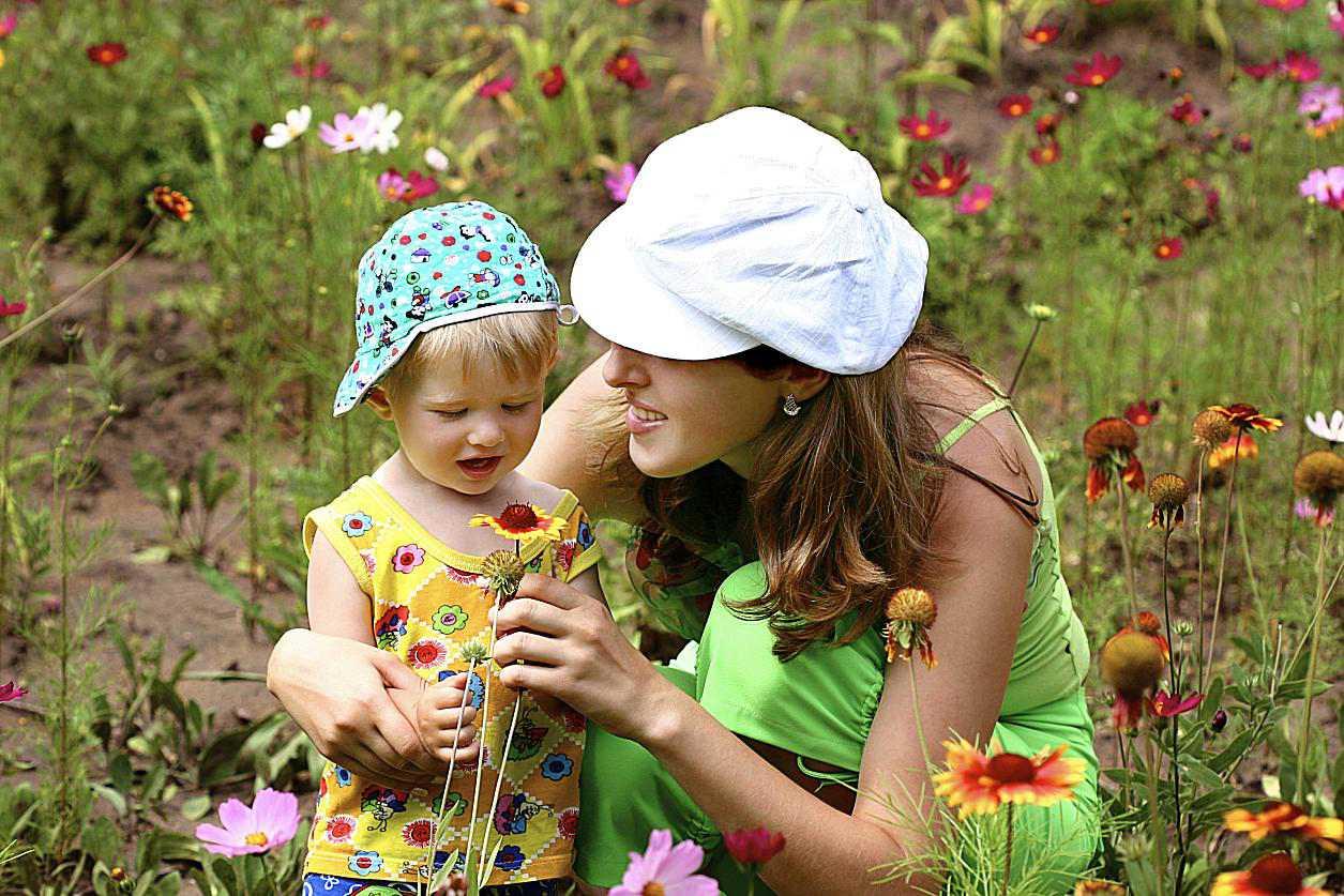 Niñera e infante en un campo de flores
