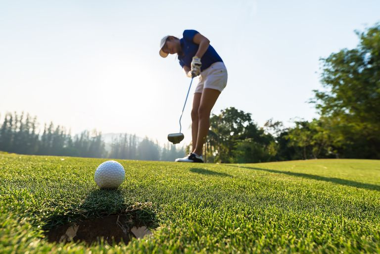 Golfing game. Asian woman golfer action to win after long putting golf ball on the green golf, sunset time, copy space. Healthy Concept