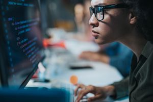 programmer reading computer codes on desktop PC.