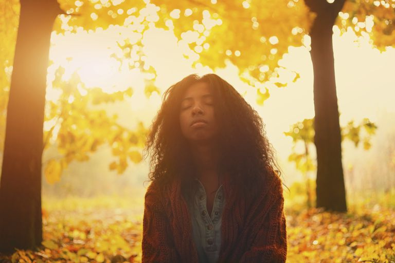 person meditating in the woods in fall