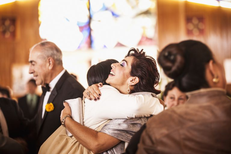 Hispanic family hugging at wedding reception