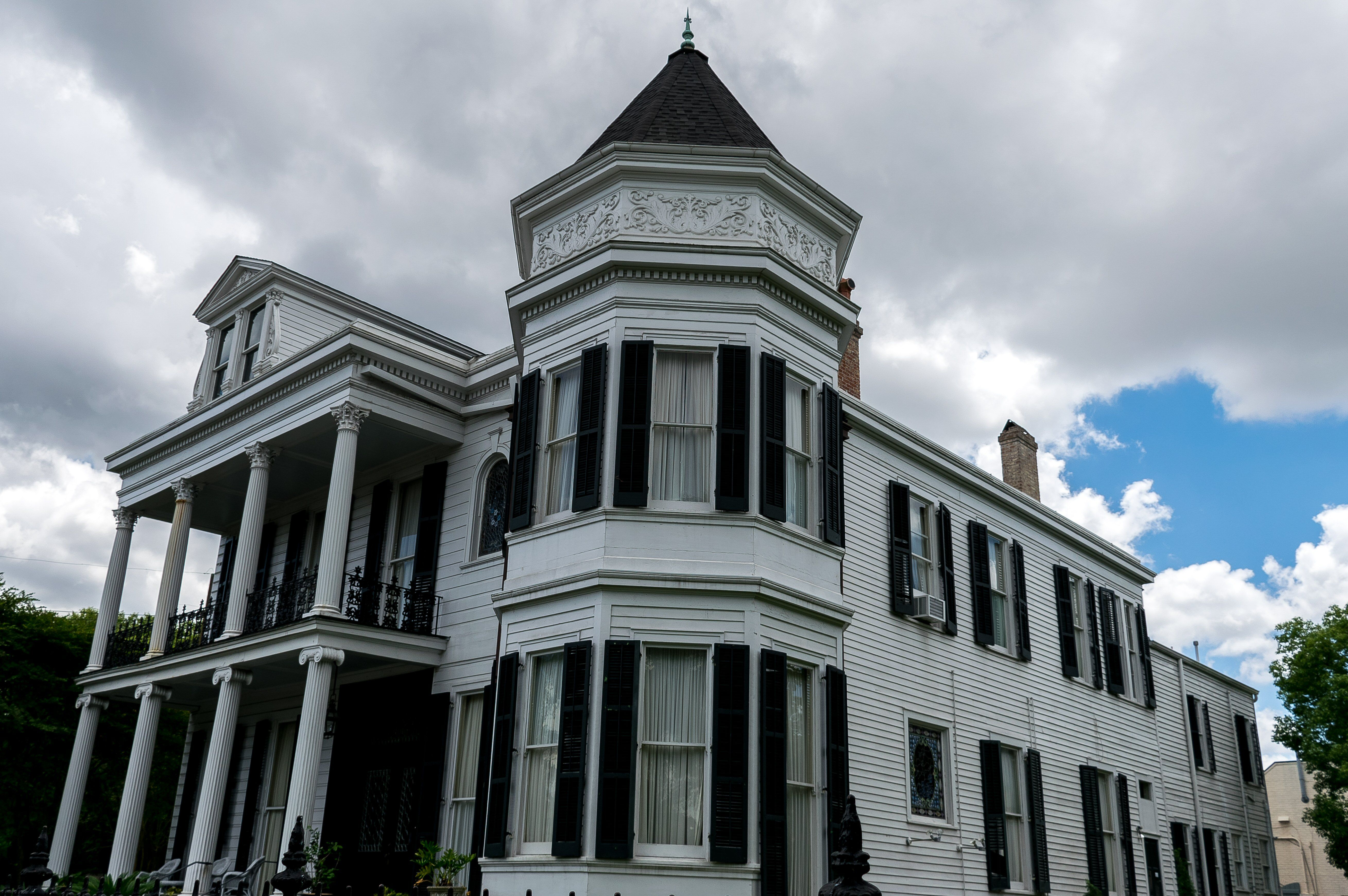 victorian house with queen anne turret near a double columned two story porch
