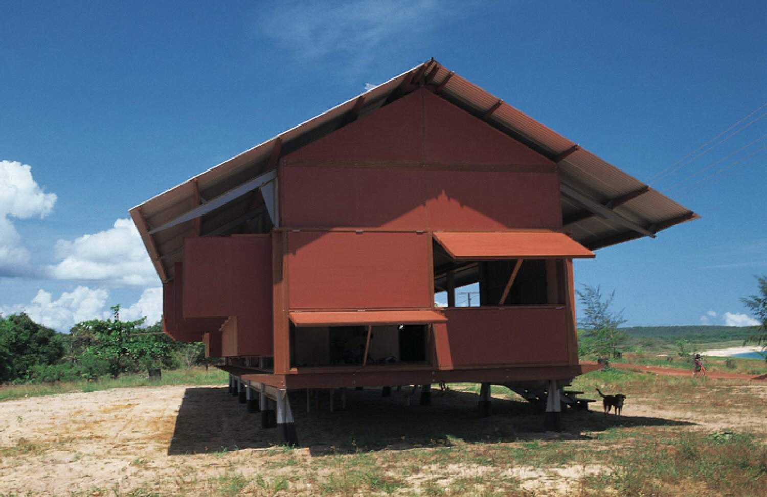 exterior of shed-like building from the narrow end, red facade with thin metal roof, large shutter openings