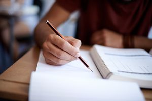 Close-up-of-young-man-writing-in-pencil-on-note-pad
