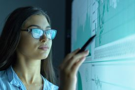 Businesswoman studying graphs on an interactive screen in business meeting