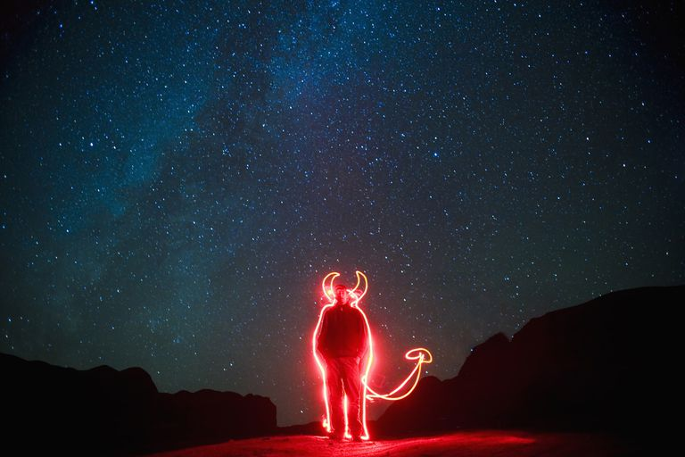 A man uses a flashlight to draw horns and a tail on himself