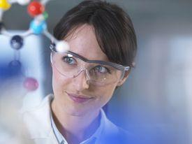 Scientist analysing molecular model in laboratory