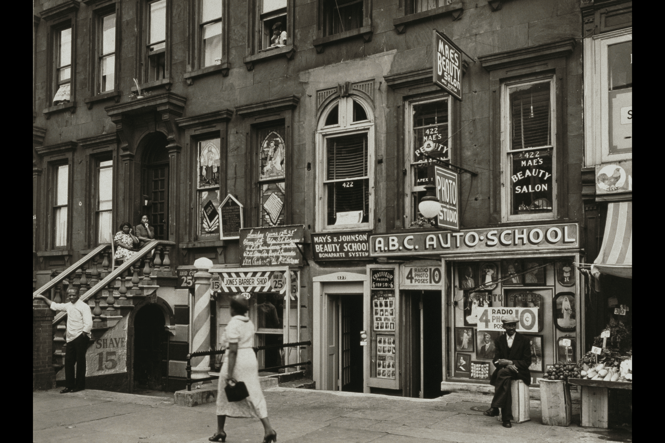 A view of storefronts on the 420 block of Lenox Avenue, Harlem, New York City, 14th June 1938. There is a barber shop, a beauty school, an auto school and a deli.