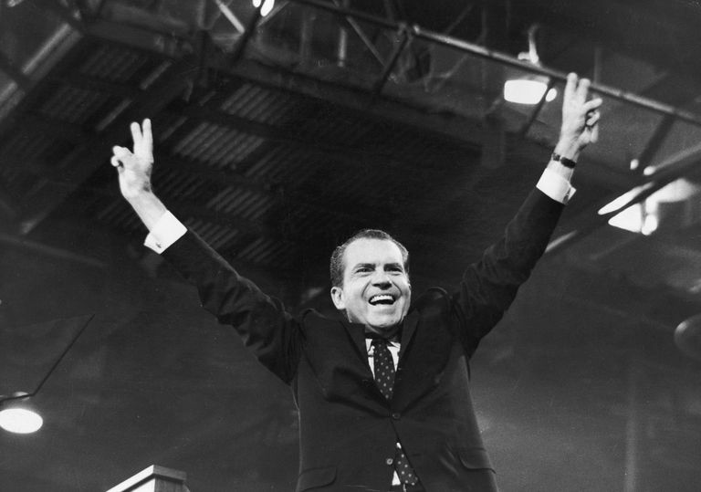 "Black and white picture of Richard Nixon raising arms up and making ""peace"" signs with his hands"