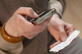 Persona con teléfono celular en mano marcando número