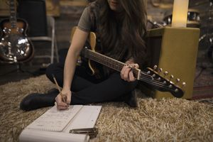 Female singer-songwriter musician with guitar writing music on rug