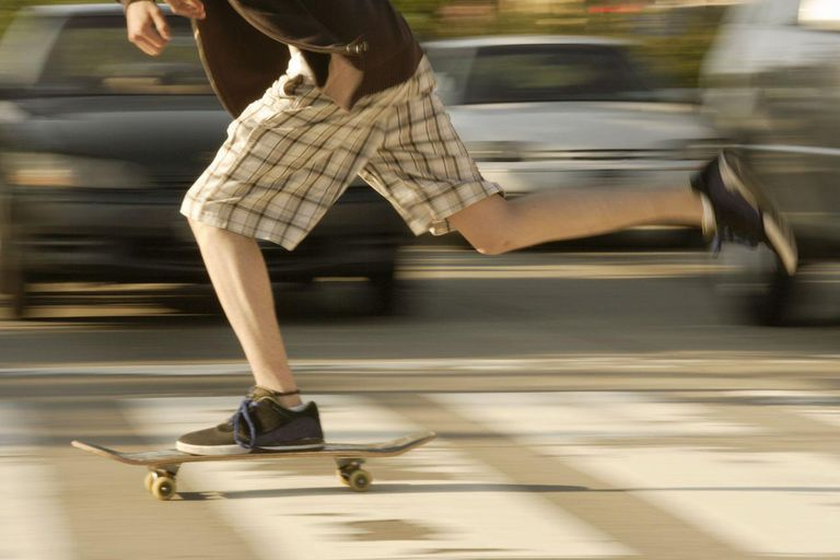 Young white male skateboarding crossing a pedestrian walkway