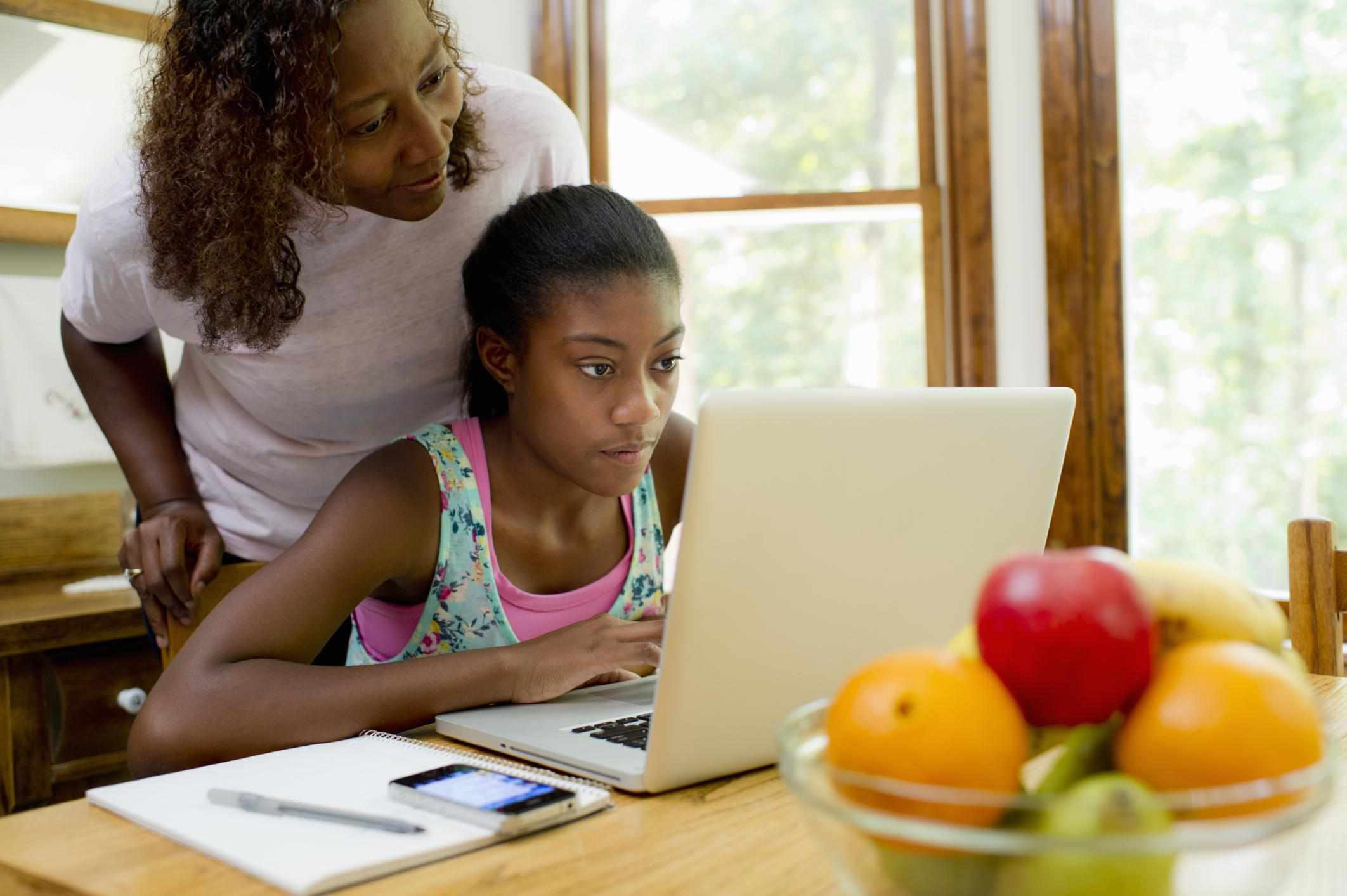 African American female teen studying with mom