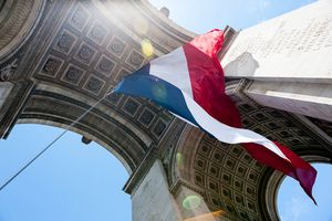 French flag under the Arc de Triomphe