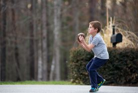 Young boy in casual clothing playing football