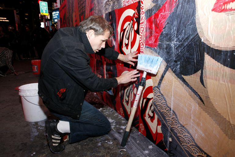 Shepard Fairey applying a poster to a wall.