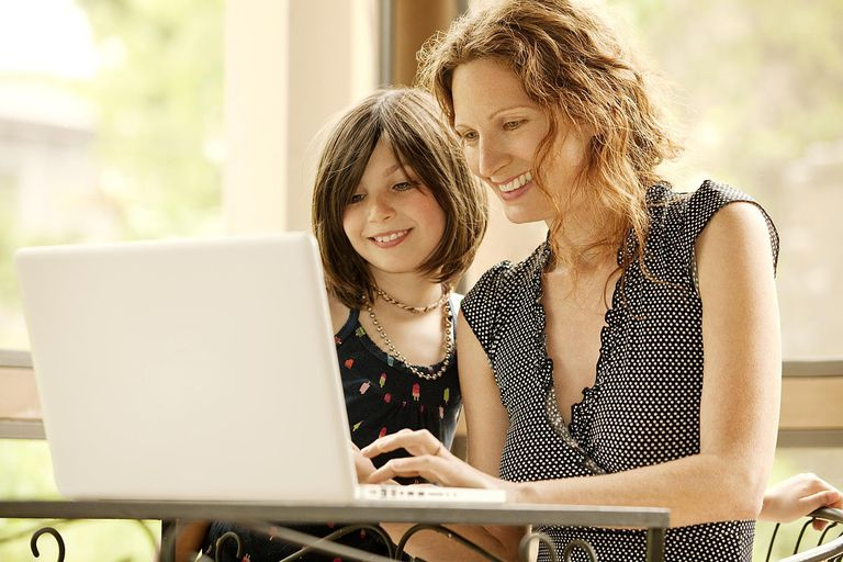 Mother and Daughter using laptop on porch.