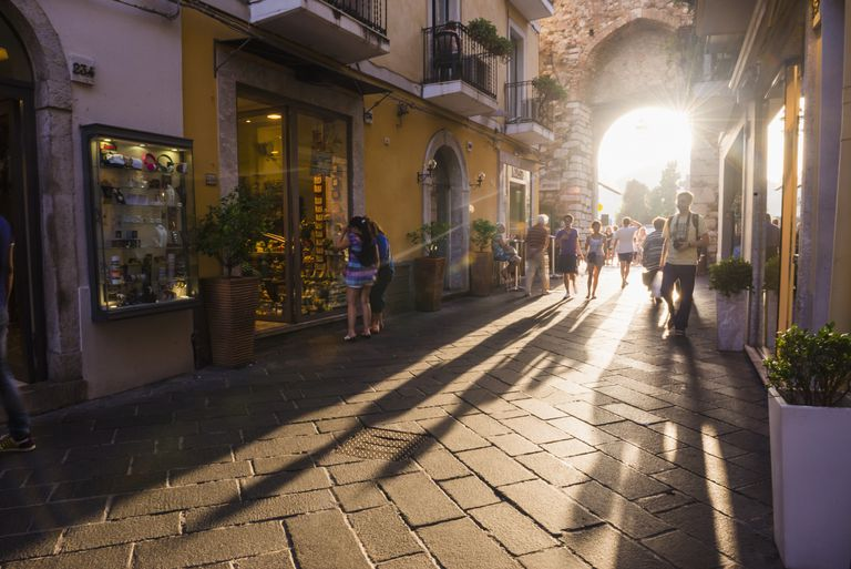 Tourists entering Corso Umberto, the main street in Taormina at sunset