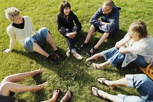 Group of young people sitting in circle on grass, elevated view