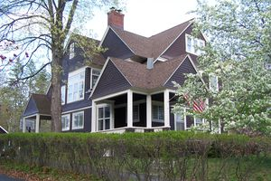 close-up of asymmetrical brown shingled home with many gables