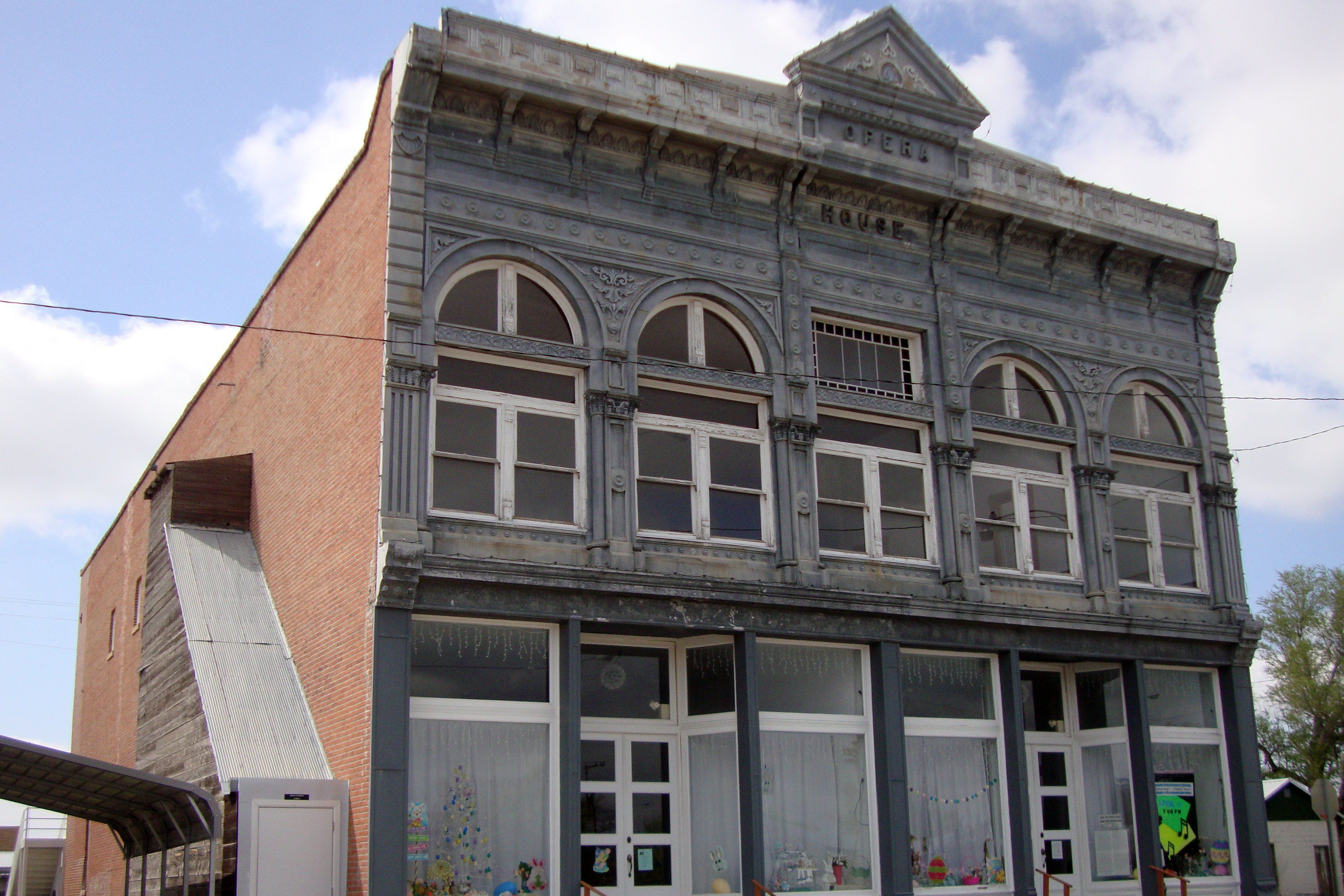 Commercial building, brick with cast iron front, large windows on facade