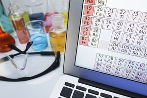 Periodic table on laptop by flask of transitional metal salts