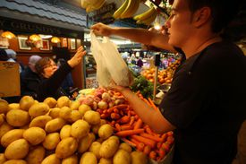 Woman purchasing produce from young man at outdoor market