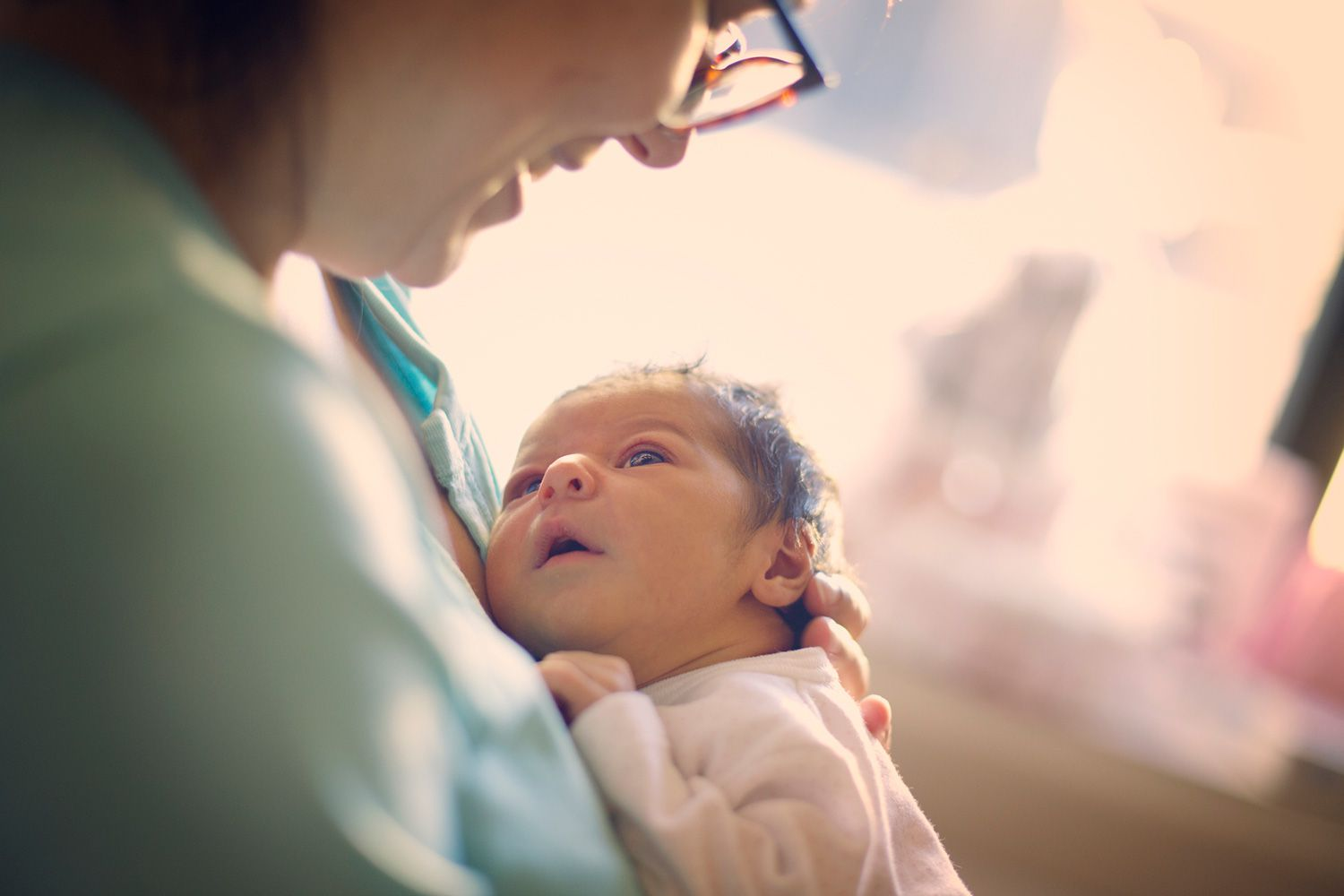 Newborn baby being held by smiling woman.