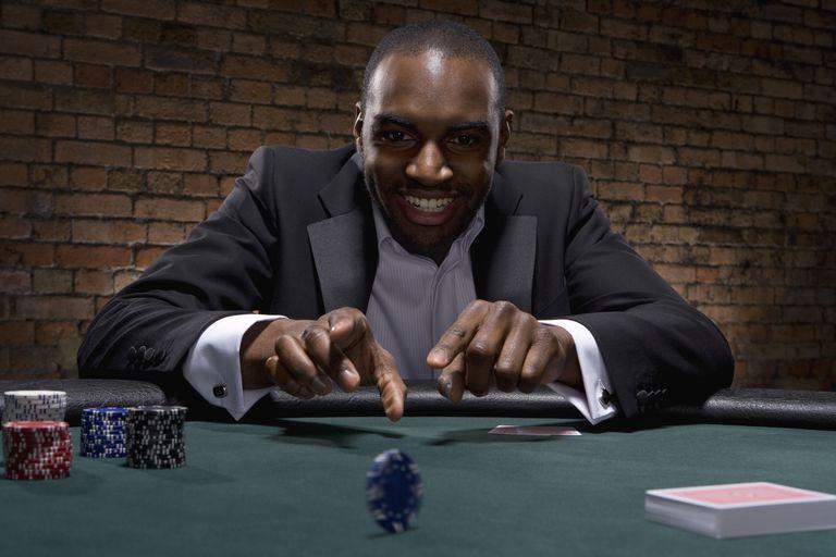Black man rolling poker chip across poker table