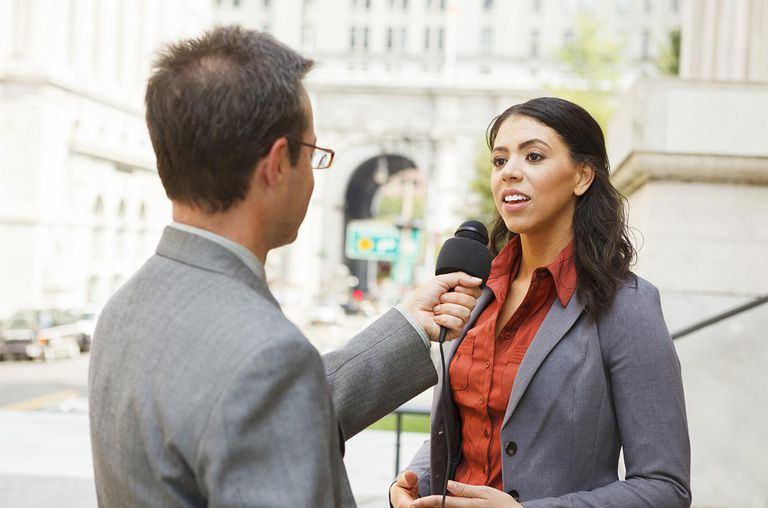 A man with a microphone interviewing a professionally dressed woman on the steps of a building in the city.