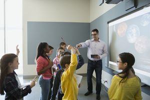 Students asking questions of a teacher leading an astronomy lesson.