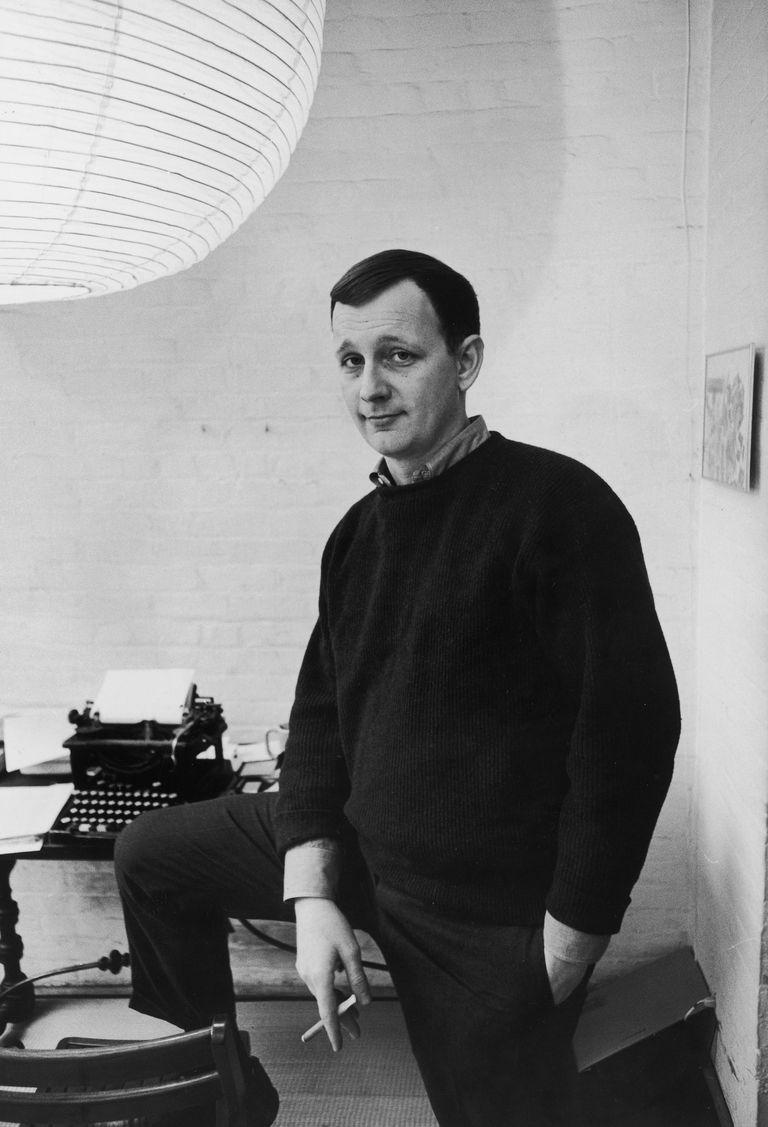Donald Barthelme smoking with leg on chair next to typewriter.