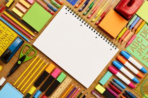 Spiral note pad surrounded by school supplies on table