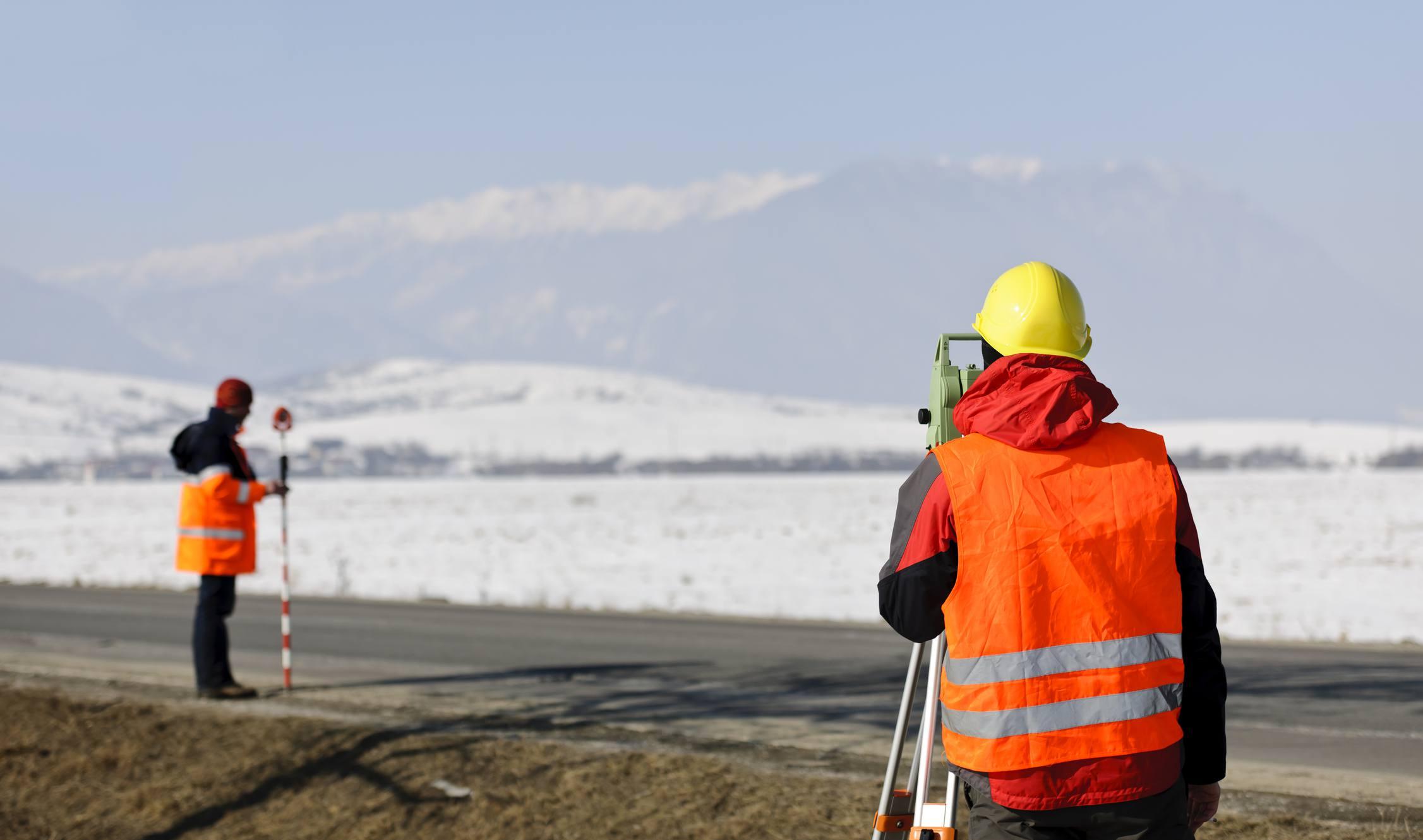 land surveyor working in winter field