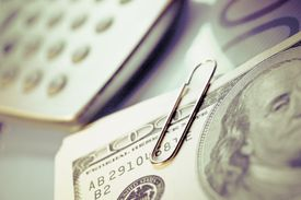 Close-up of US paper currency and a calculator